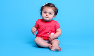 A baby poses in a bright pink onesie on an all blue background. Callie, who is almost 1, was born with the help of in vitro fertilization.