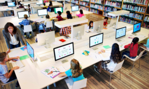 A stock photo shows a top-down angle of a library, where abut 10 young students sit around a table, each in front of their own computer.